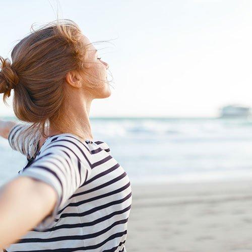Frau steht am Strand und ist gluechklich