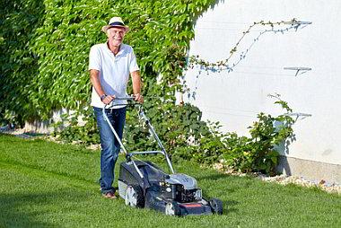 Pensionär mit Rasenmäher und Hut
