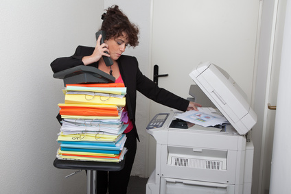 Angestellte steht am kopierer und telefoniert