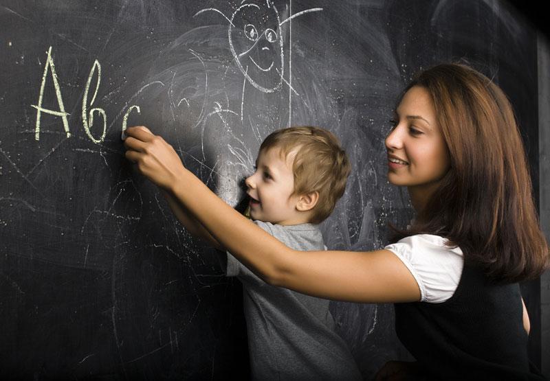 Lehrerin schreibt mit Schüler auf die Tafel