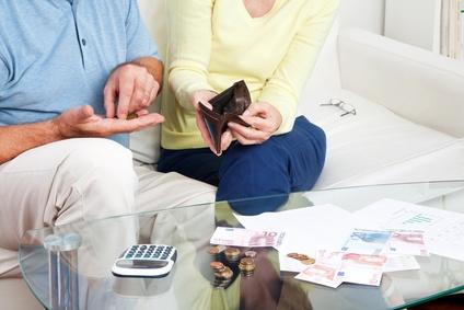 Älteres Paar zählt Geld auf dem Wohnzimmertisch