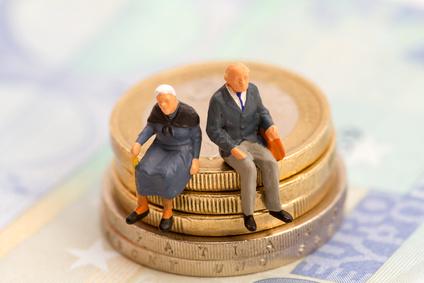 Senioren sitzen auf Muenzstapel