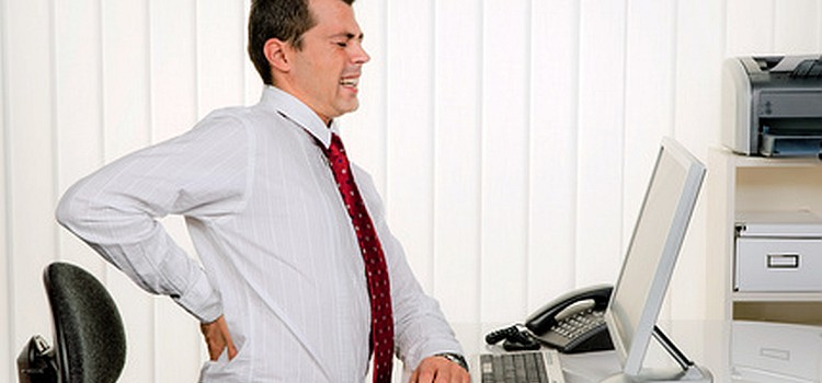 Dienstunfähigkeit Mann im Büro mit Rückenschmerzen