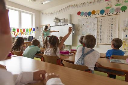 Lehrerin zeigt auf die interaktive Tafel. Grundschüler lernen und eine Schülerin meldet sich