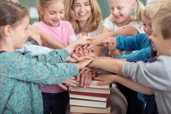 Schulkinder mit Ihrer Lehrerinvhülern im Unterricht