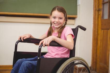 Behinderte Schülerin im Rollstuhl lächelt