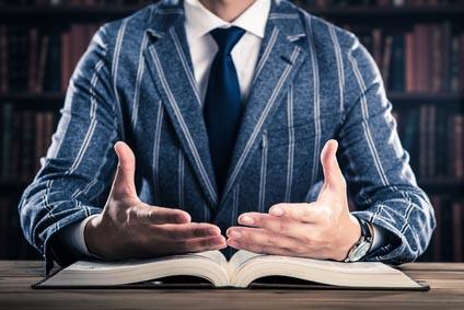 Mann sitzt vor einem geöffneten Buch
