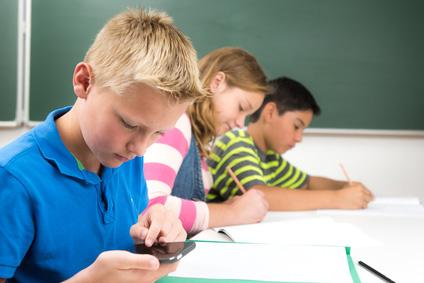 Schulkind mit Smartphone im Unterricht