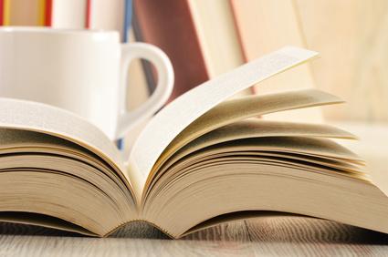Buch und Tasse auf dem Schreibtisch